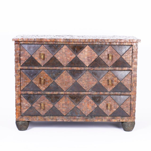 A three drawer chest or commode entirely clad with a coconut shell mosaic with harlequin drawer fronts and set on faux...