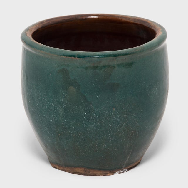 A luminous blue-green glaze sheets, pools, and drips down the surface of this pickling pot, lingering beautifully on every...