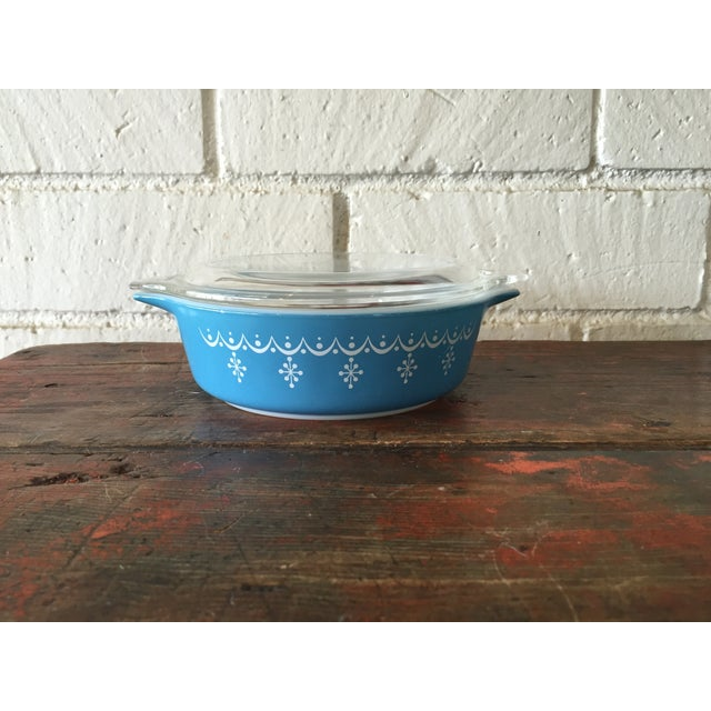 Round, glass Pyrex casserole dish with clear glass lid. The exterior of this piece features the Snowflake Garland pattern....
