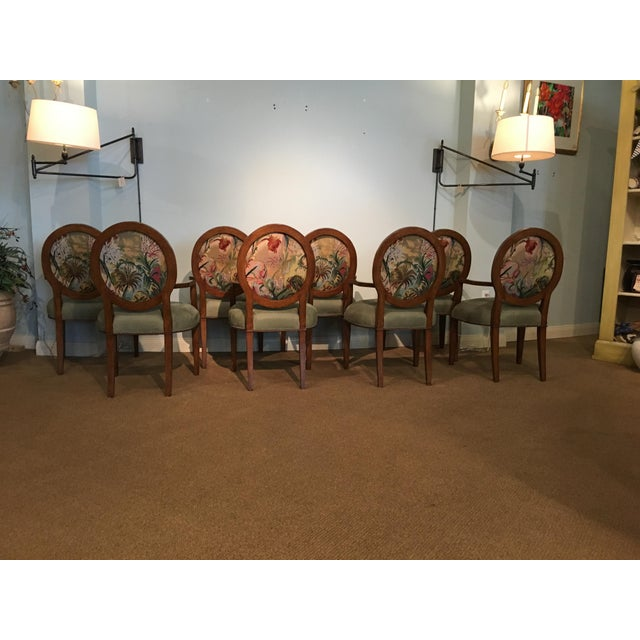Set of eight wood frame arm chairs in a rich mahogany finish. Chairs feature a tight seat cushion and tight inside back...