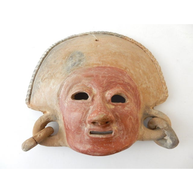Pre Colombian style crowned mask with red face, shows signs of restoration in one earring . This artifact would look...