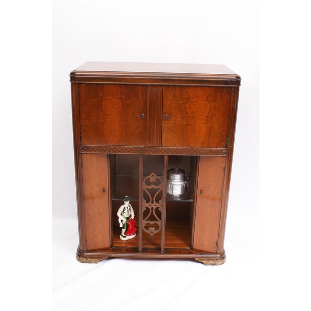 This funky cabinet started life as a radio, with controls inside the upper doors and speakers below behind the fretwork...