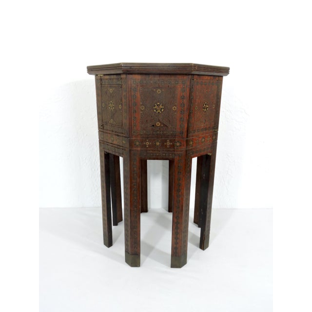 An old Morrocan side table or stool intricately inlaid with mother of pearl, fine brass wire and other exotic woods, in...