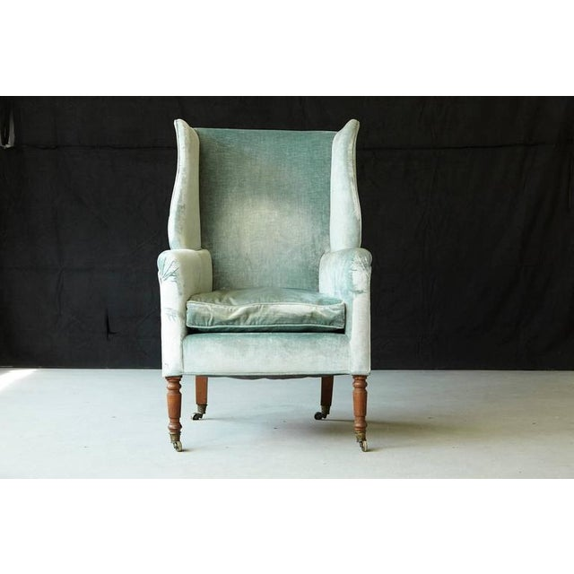 Early 19th century Hepplewhite mahogany wingback chair on brass casters, upholstered in silver striae velvet.