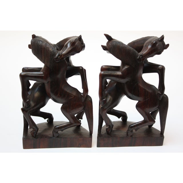 Pair of exquisite horse sculptures / bookends depicting two entwined / conjoined horses. Sculptured from iron wood (an...