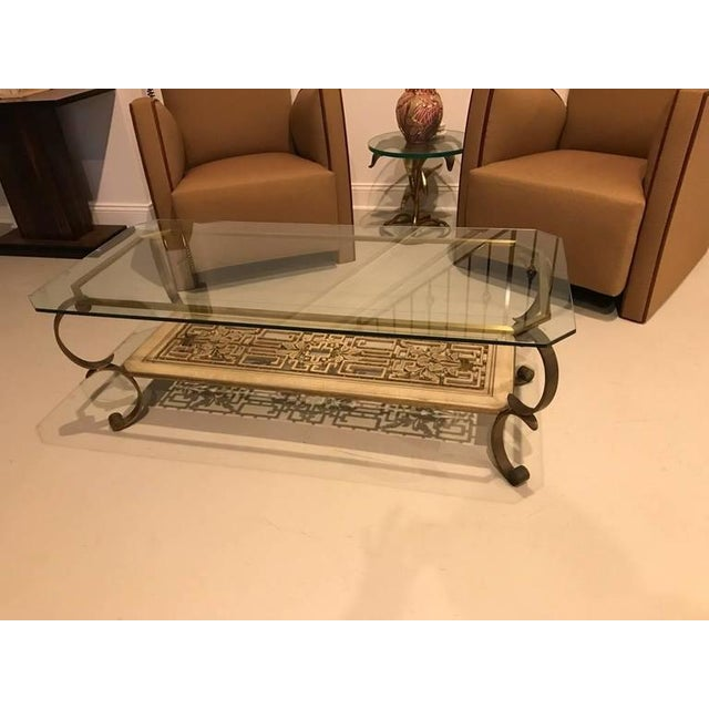 Mid-Century Modern brass and giltwood coffee table. Having antique brass legs with a bottom hand-carved and painted...