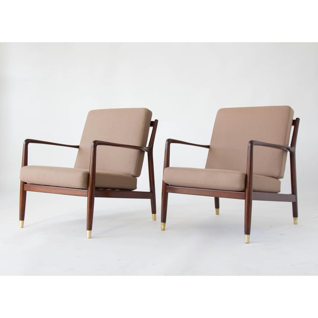 A pair of dark-stained teak lounge chairs designed by Folke Ohlsson and imported to the US under the DUX name. The chair...