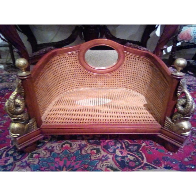 1960 caning wicker dog bed with cushion. The bed has a small mirror above it. On the side of the dog bed are two koi fish.