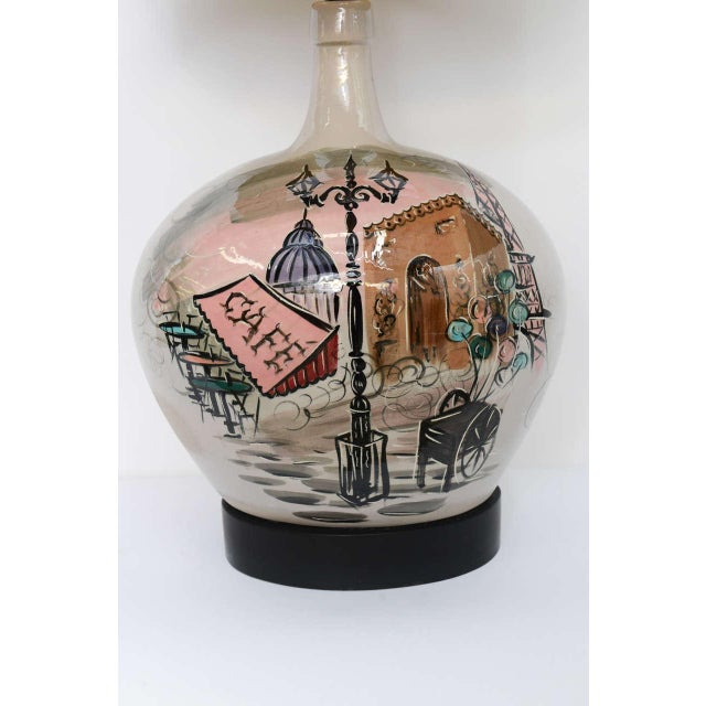 Grand scale with this charming 1950s bulbous pottery table lamp with an underglaze painted Parisian scene. Illegibly...