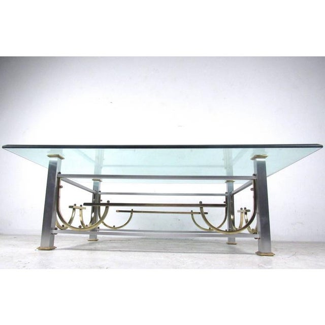 This unique vintage coffee table features a stylish vintage base with four post design, beveled glass and brass trim....