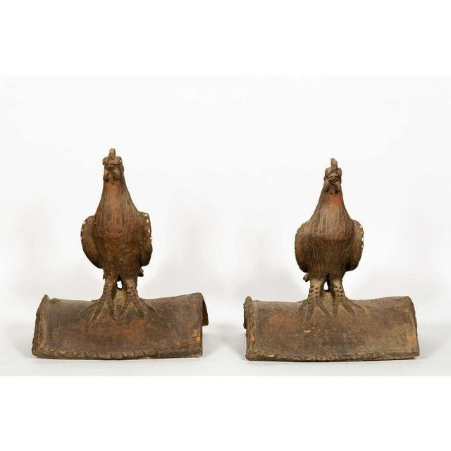 A pair of terra cotta rooster corner roof tiles. Wings and eyes are embellished with glazed shards. Unmarked but I believe...