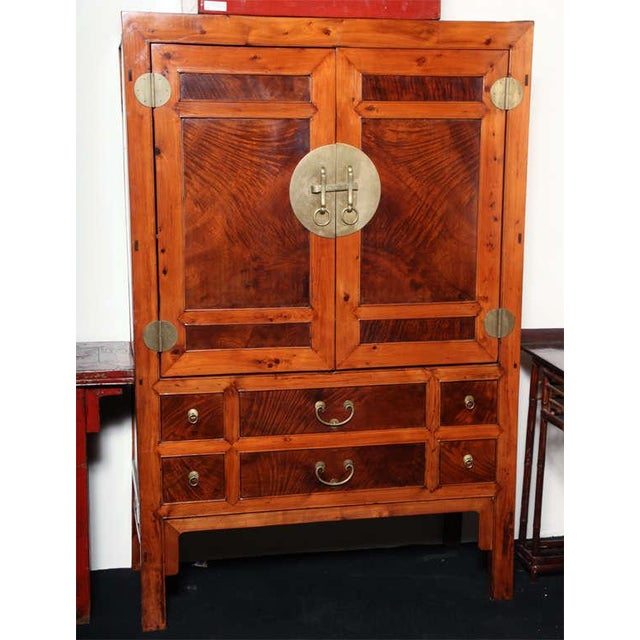 A large Chinese turn of the century burled wood cabinet with two doors and multiple drawers. This large cabinet made with...