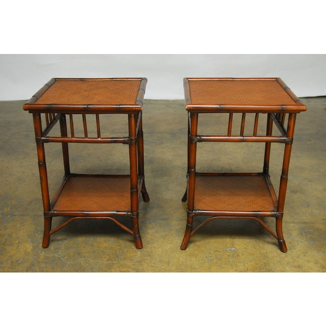 Handsome pair of rattan side tables featuring two tiers with a lacquered sea grass top. Open fretwork decorated sides with...