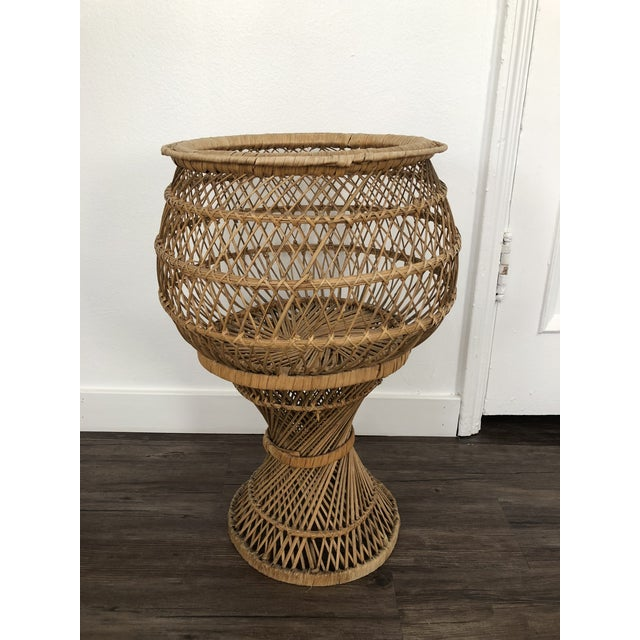 1970's wicker plant stand is a charming piece of vintage garden decor. Tulip shaped, it has a cottage chic meets victorian...