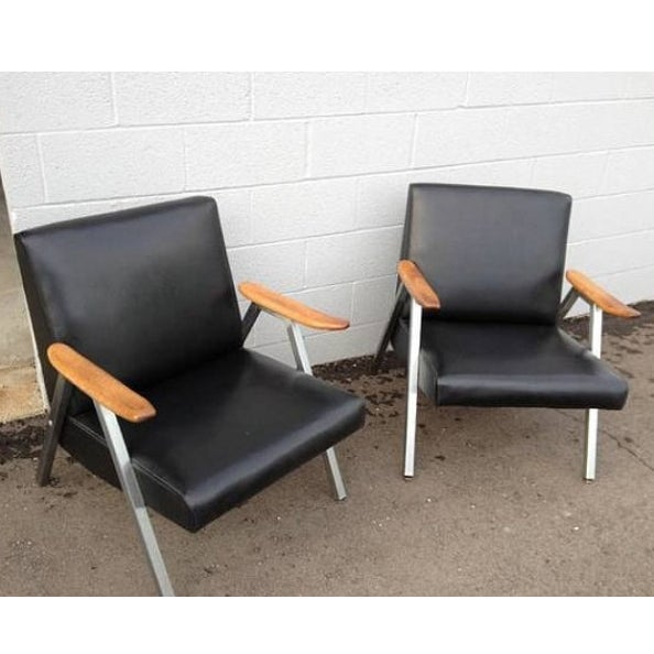 Mid-century low profile vinyl black chairs with wood arms and steel frames. No holes or tears in vinyl. Normal age...