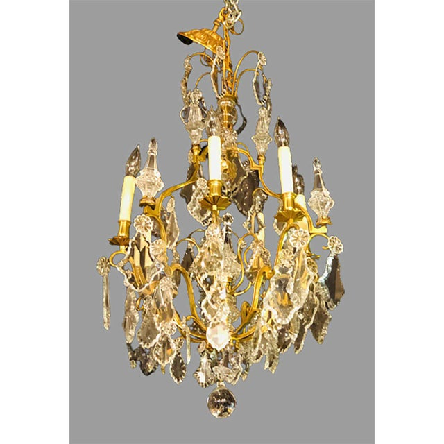 French bronze and crystal gilt chandelier. Louis XVI style six-light chandelier having a glass column-form center with...
