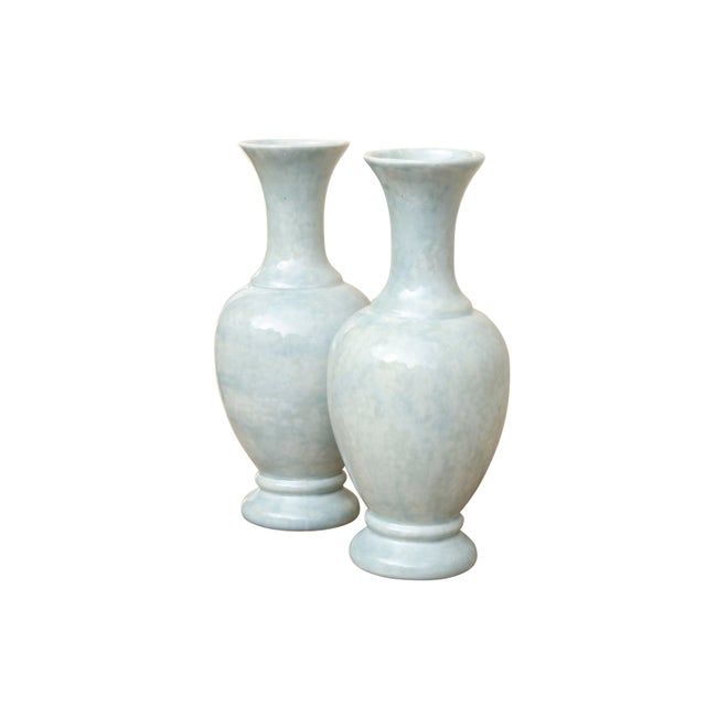 A pair of ceramic vases in pastel mint. The vases have tall slender necks and elegant urn shapes with a light mottled...