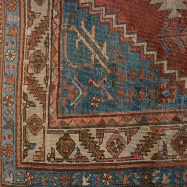A 19th century Persian Bakhshayesh carpet with a multi-layered central medallion with an indigo frame surrounded by a...
