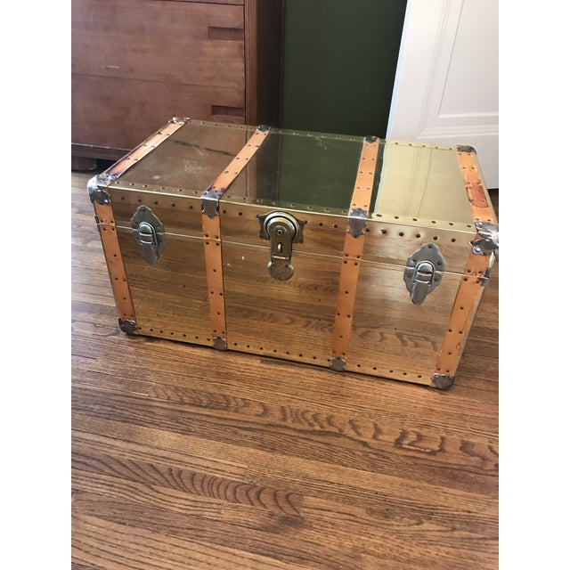 Brass trunk with leather strapping. This piece would make an excellent coffee or side table. ** KEY IS MISSING AND TRUNK...