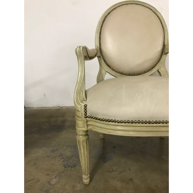 Antique wood and upholstered side chair. Cream leather upholstery, nail head detail