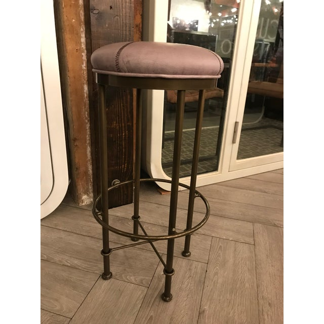 Tall, painted brass barstools with large, unique cross-stitching over a gray leather seat. These stools are versatile and...