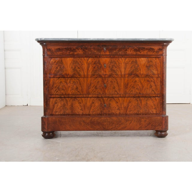 This elegant and restrained Louis Philippe flame mahogany four-drawer commode, c.1830's, is from France and has a gorgeous...