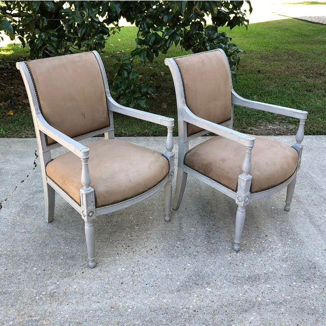 Pair 19th Century French Louis XVI Painted Armchairs are an excellent example of the neoclassical style, and feature...