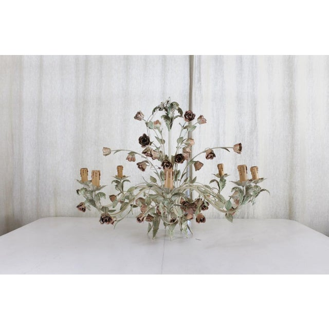 A beautiful Mid-Century Hollywood Regency Italian toleware eight-arm chandelier. The soft muted colors in the vines and...