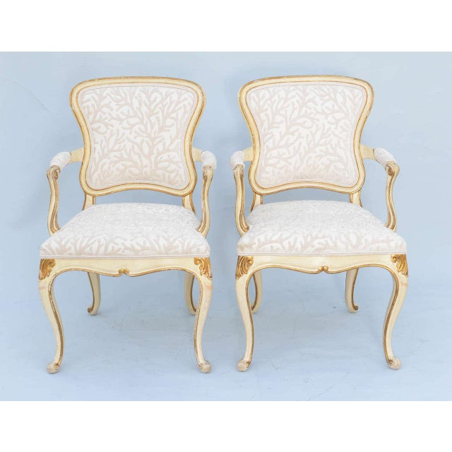 Pair of Venetian style armchairs, each having a painted frame with parcel gilt details; free-form shaped padded back in...