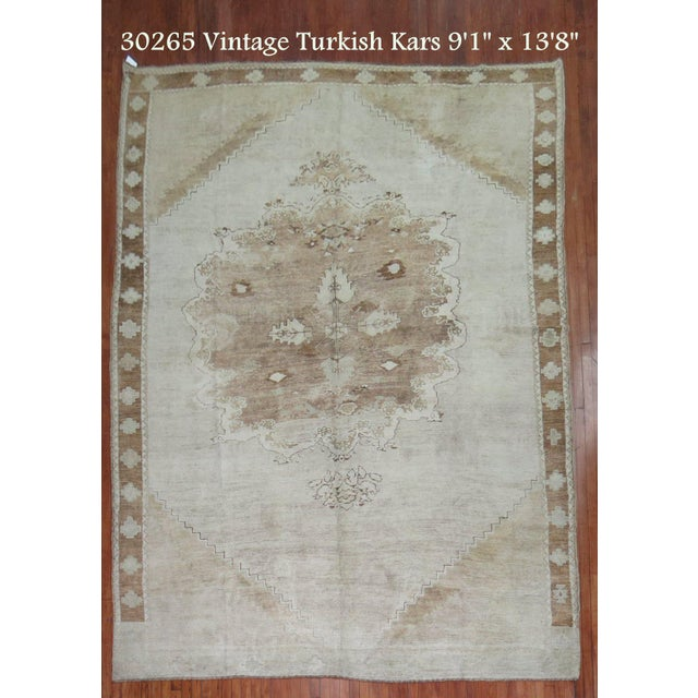Hand-woven mid 20th century Turkish Rug with a floral medallion and border motif in ivory and brown. Rug has full even...