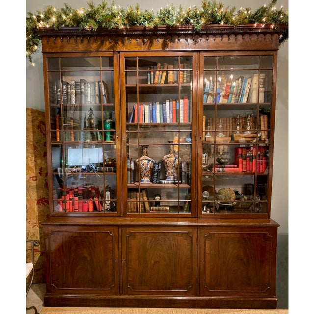 A 1750 Chippendale mahogany breakfront with three glass doors and lower cabinets. With key, from England.