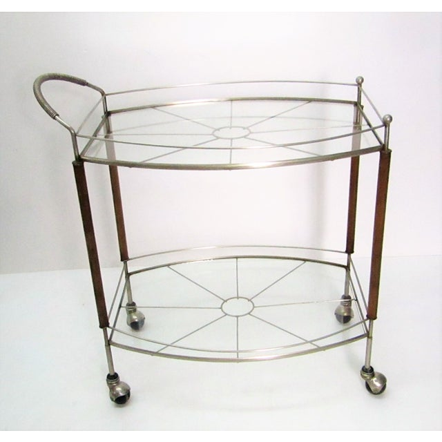 Sleek mid century modern bar car/ tea cart featuring teak legs and metal supports. The handles have a wrapped metal...