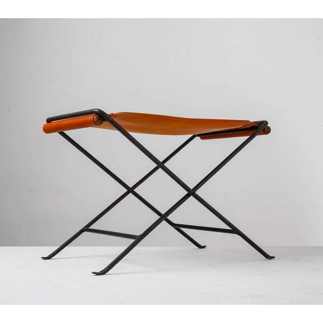 A foldable stool made of a black iron frame with a brown leather sling seat, by Californian designer Cleo Baldon. The...