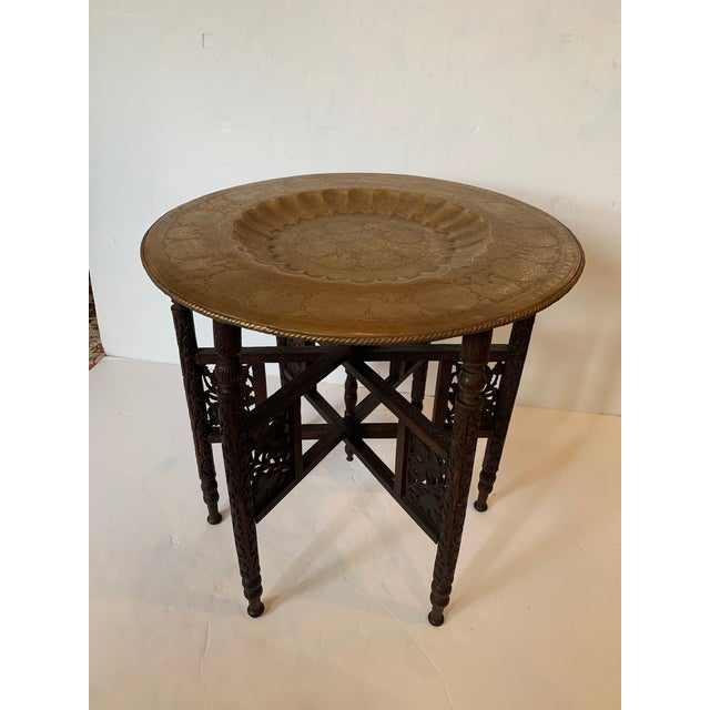 Exotic Moroccan tray top end table having beautiful etched brass tray with central recessed scalloped circle and folding...
