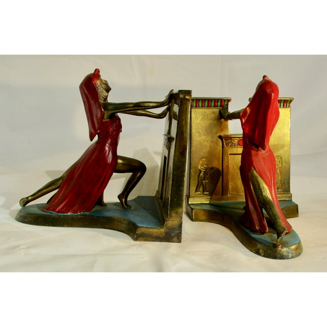 Beautiful bronze bookends , romanticize the Egyptian revival. Polychrome red and teal blue. Art Deco stylized female...