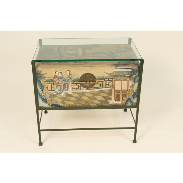 Chinese polychrome decorated pigskin trunk mounted on an iron stand with a glass top. The pigskin trunk was made in China,...