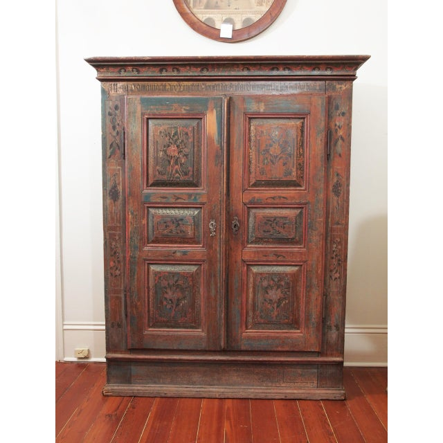 An armoire with paneled doors and well molded cornice. Retaining the original paint, now worn, but of hues of reds and...