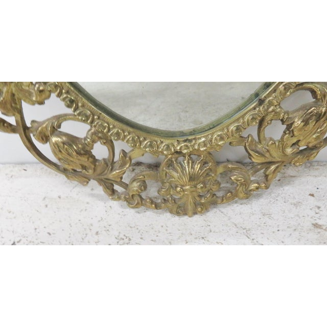 Brass frame with cherub on crest with floral.