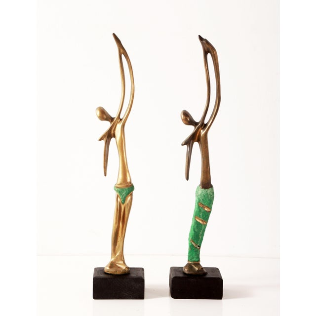 Stunning pair of sculptural cast bronze figures depicting a man and woman, from the country of Angola, c.1970's. They are...