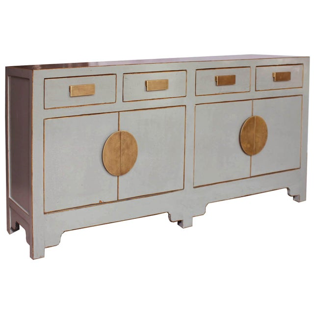 Place this contemporary gray sideboard with subtle crackle finish, bold brass hardware, exposed wood edges and clean lines...