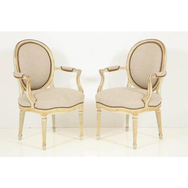 A beautifully crafted pair of Louis XVI Style fauteuils with oval backs, a serpentine front, a fluted apron and fluted,...