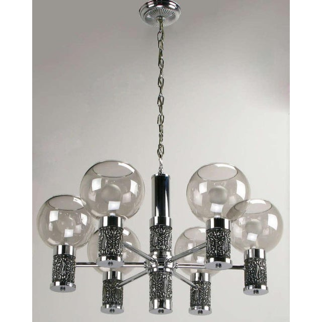 Six arm chandelier combines chrome plated metal and cast chrome plated relief. Cylinders at the center and on each arm are...