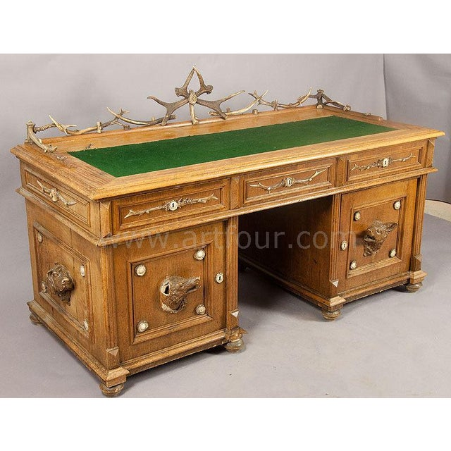 antique oak wood desk decorated with several antler pieces. the doors and sides carry mass animal heads (staghound and...