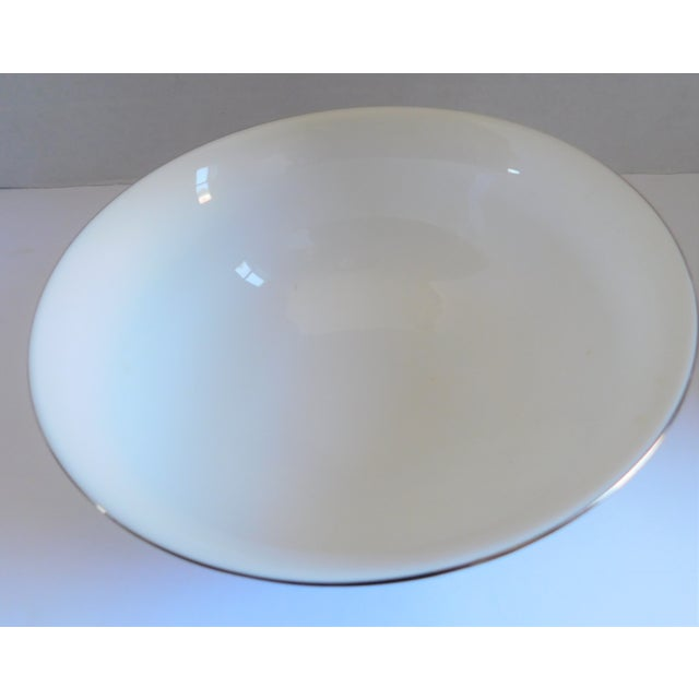 This sparsely elegant Kate Spade for Lenox white vintage porcelain serving bowl with silver ribbon swirls is part of her...