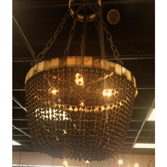 Absolute Showstopper! This beaded chandelier by Noir is a great rendition of the bead chandelier. It is made of heavy grey...