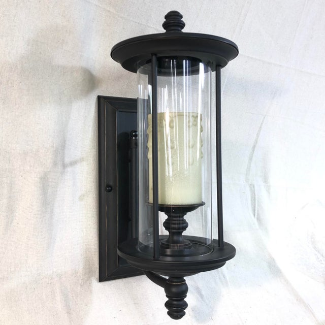 This outdoor wall lantern features an English Bronze finish with a cream scavo glass candle that will add warmth and...