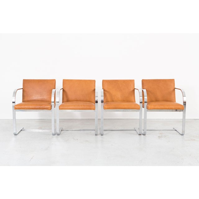 A set of four cantilever dining chairs designed by Thonet in the USA, c 1960s. Full grain pull-up leather and chrome....