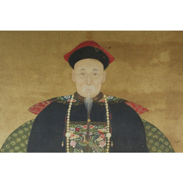 Symmetrical Chinese ancestor painting in black frame with gold accents. The piece dates back to the early 20th century.
