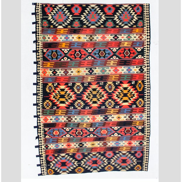 This traditional vintage Turkish kilim rug measures 5.4' x 8' and is woven in shades of blue, red, green, yellow, black,...