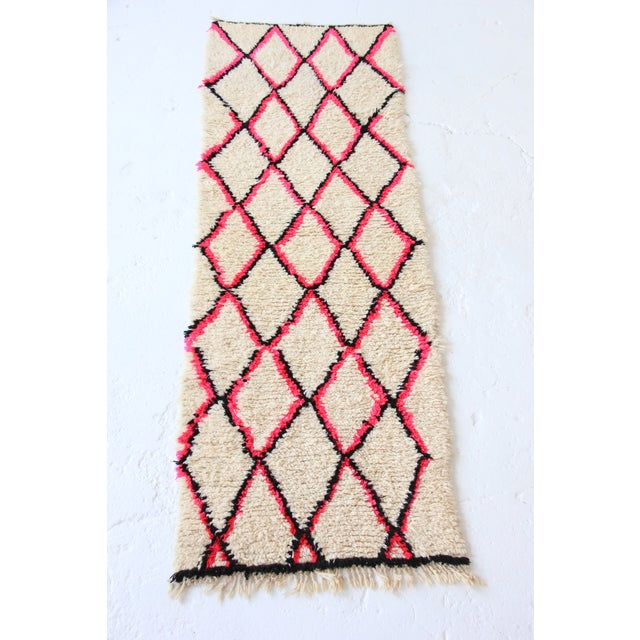A gorgeous, vintage Beni Ourain Moroccan runner rug featuring a beautiful, off-white cream color with a bright pink and...